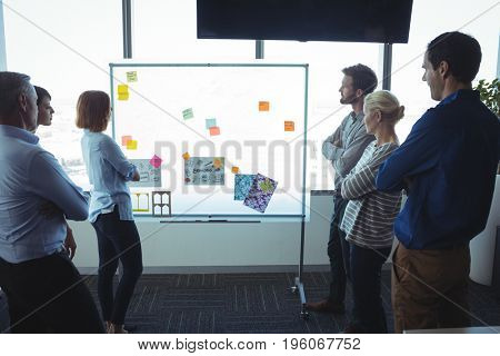 Business people looking at adhesive notes on whiteboard at office