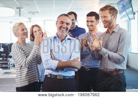 Happy businessman standing with arms crossed while colleagues clapping around him at office