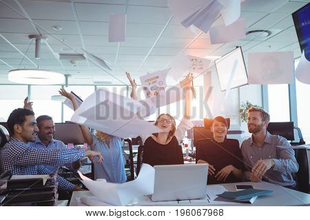 Happy business people tossing papers in air at desk