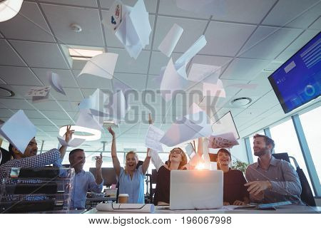 Cheerful business people tossing papers against ceiling in office