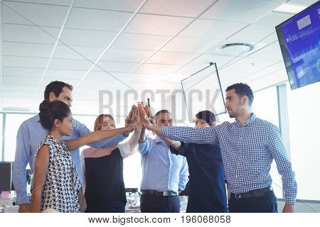 Business colleagues putting their hands together at office