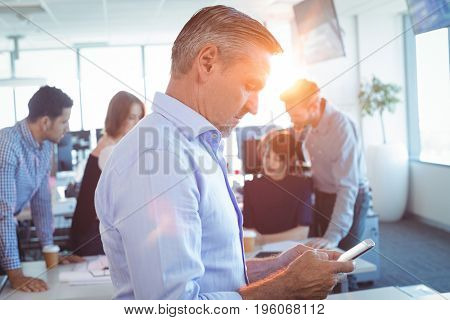 Side view of businessman using mobile phone with team in background at office