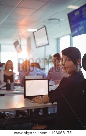 Portrait of young businesswoman working on laptop at desk in office
