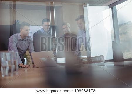 Business colleagues seen through glass discussing around desk during meeting in board room
