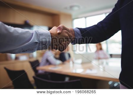 Cropped image of business people shaking hands during meeting in board room