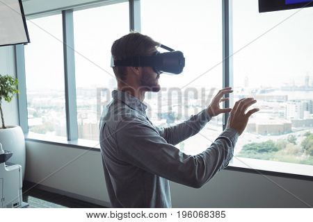 Side view of businessman using virtual reality glasses at office