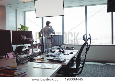 Businessman taking on mobile phone by glass windows at office