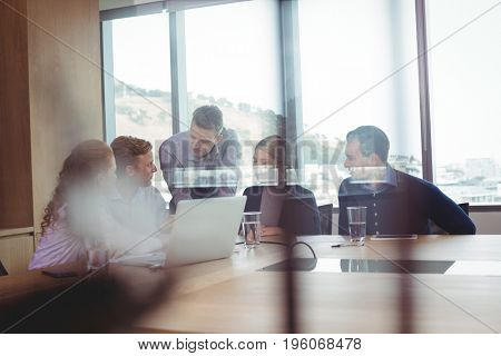 Business people discussing in board room seen through glass at office