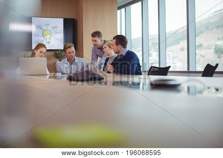 Business people discussing at desk in board room