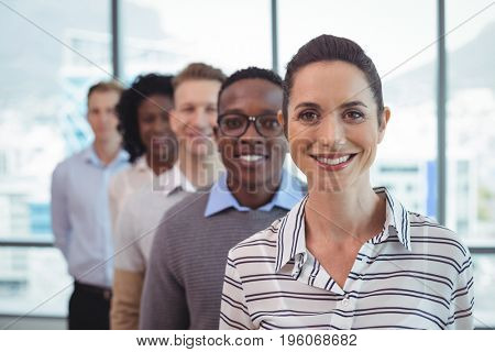 Portrait of smiling business colleagues standing in row at office