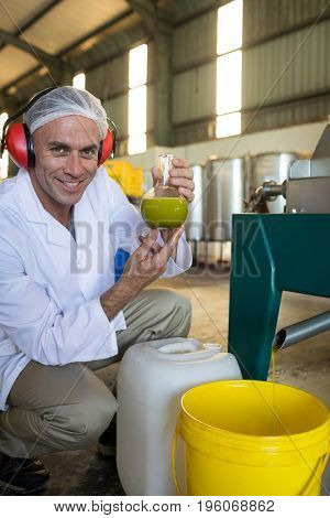 Technician examining olive oil produced from machine in factory
