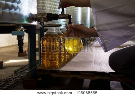 Mid section of female technician examining olive oil in factory