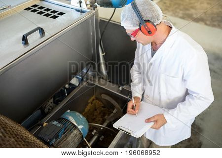 Technician examining processing machine in oil factory
