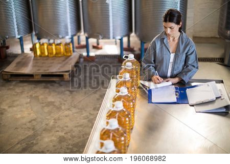 Female worker maintaining record in notepad at factory