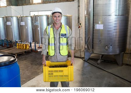 Portrait of happy worker holding harvested olives in crate at factory