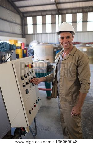 Portrait of happy technician operating a machine in oil factory