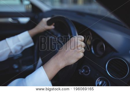 Cropped image of businesswoman driving car