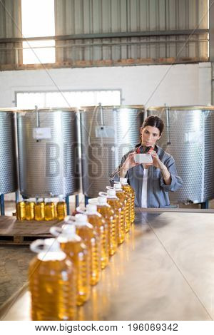 Female worker taking photo of oil bottles from mobile phone in oil factory