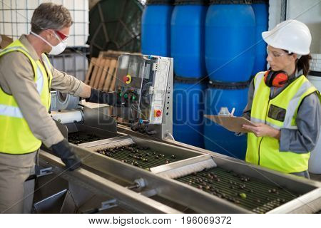 Technicians operating machine while processing olives in factory