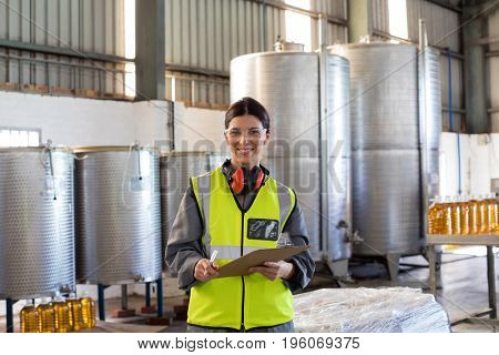 Portrait of female technician writing in clipboard at oil factory