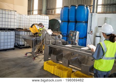 Technician and worker working together in oil factory
