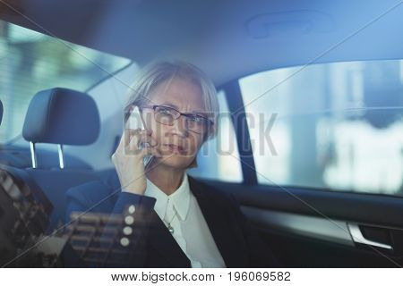 Businesswoman talking on phone while traveling in car