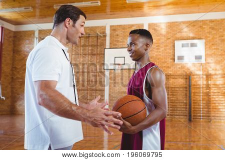 Coach talking with basketball player while standing in court