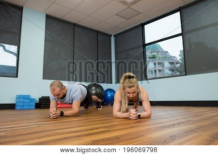 Young friends exercising on hardwood floor at gym