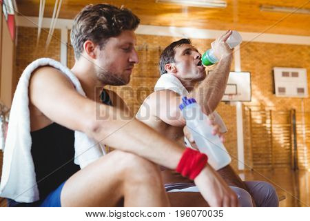 Friends drinking water while sitting on bench in court