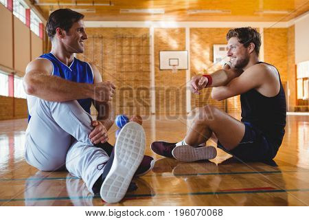 Happy male friends practicing stretching exercise while sitting on floor in court