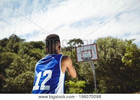 Rear view of male teenage boy practicing basketball in court on sunny day