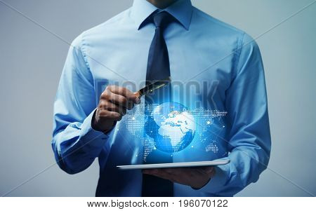 Concept of management information systems. Man with tablet and magnifier on color background