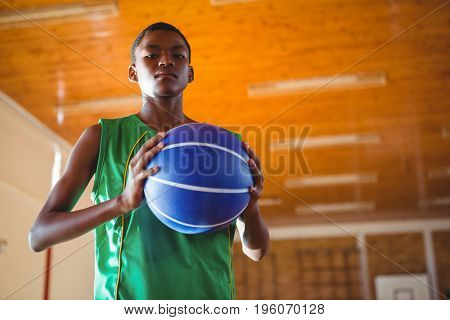 Low angle portrait teenager holding ball while standing in court