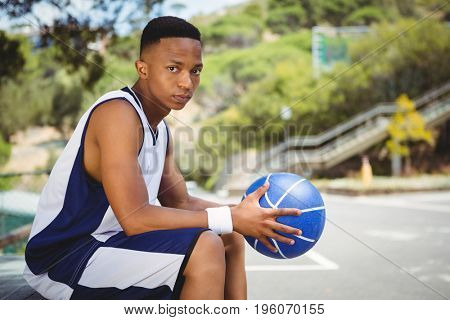Portrait of teenage boy with basketball sitting on bench in court