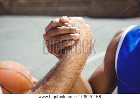 Cropped image of basketball players holding hands while playing in court