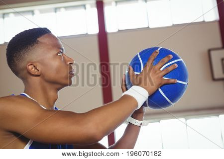 Close up of male teenager with basketball in court