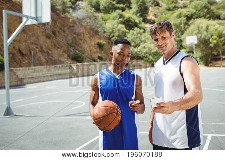 Friends talking selfie while standing in basketball court