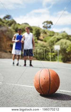 Basketball on ground with player standing in background at court