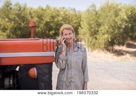 Portrait of happy woman talking on mobile phone in olive farm on a sunny day