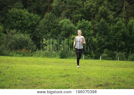 Smiling young woman exercising on running path in green summer park