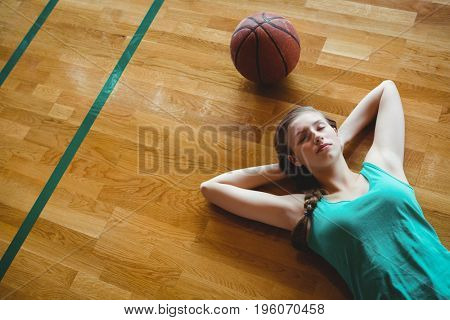 Overhead view of female basketball player sleeping in court