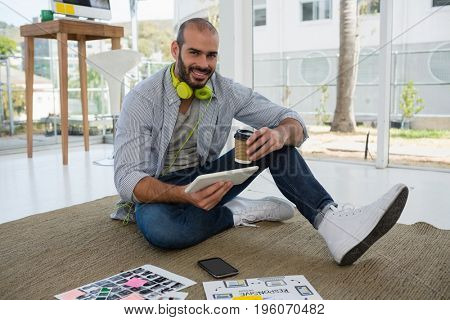 Portrait of designer holding disposable cup and tablet computer while sitting on floor