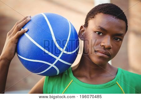 Close up portrait of teenage boy with basketball on shoulder