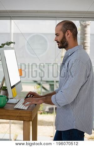 Side view of male designer using computer while standing in studio