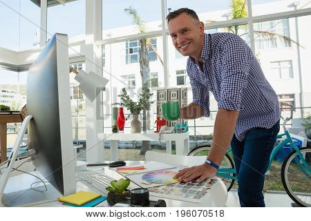 Portrait of designer holding coffee while standing at table in office
