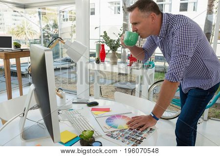 Designer looking at computer while having drink in studio