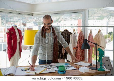 Male designer drawing sketch at table in workshop