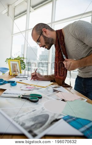 Male designer drawing sketch while standing at table in studio