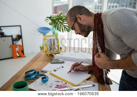 Male designer drawing sketch while standing at table in workshop