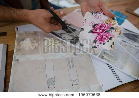Cropped hands of designer cutting papers at table in studio